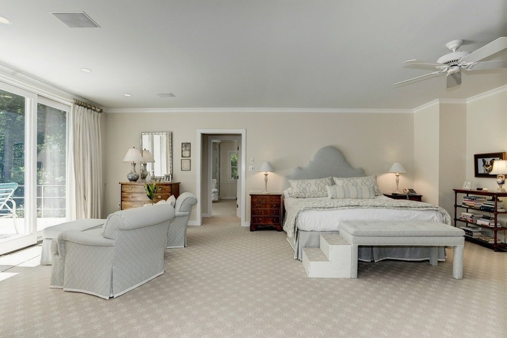 This spacious primary bedroom has a large bed with a gray cushioned headboard that matches the light gray cushioned armchairs on the side of the sliding glass doors. Image courtesy of Toptenrealestatedeals.com.