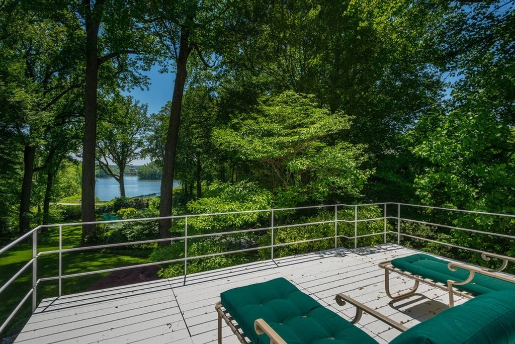 This is a deck terrace fitted with a couple of cushioned lawn chairs to better enjoy the surrounding landscape of tall trees and the view of the reservoir in the distance. Image courtesy of Toptenrealestatedeals.com.