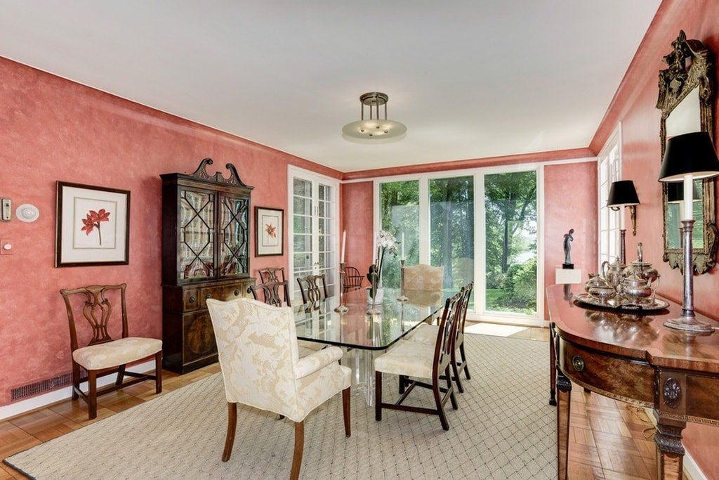 This is the formal dining room with a large glass-top dining table surrounded by beige cushioned chairs that stand out against the chic pink walls of the dining room. Image courtesy of Toptenrealestatedeals.com.