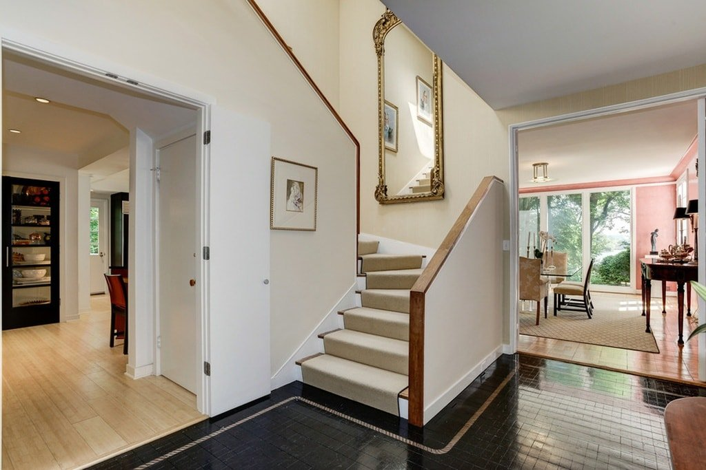 This is the simple foyer with a black flooring that contrasts the white walls and white ceiling. These are then adorned with wall-mounted decors by the stairs. Image courtesy of Toptenrealestatedeals.com.