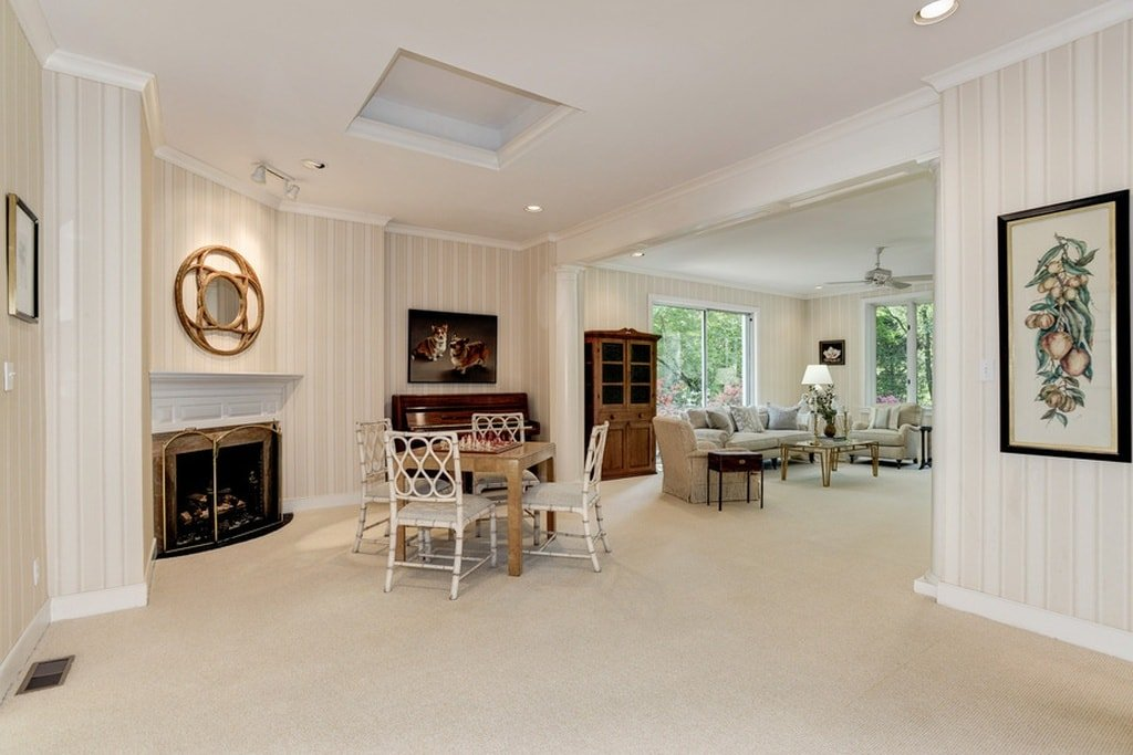 This is the game corner just a few steps from the living room. It has a table for board games like chess beside a fireplace that is adorned with a wall-mounted artwork above its white mantle. Image courtesy of Toptenrealestatedeals.com.