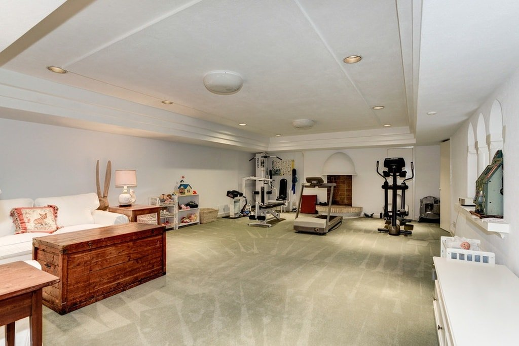 This is the spacious gym of the house that has machines on a beige carpeted flooring that is brightened by the white walls and white ceiling with recessed lights. Image courtesy of Toptenrealestatedeals.com.