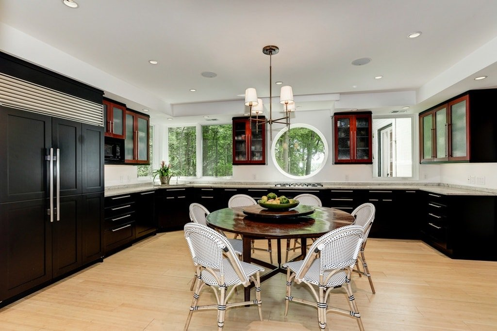 This kitchen has black cabinetry that stands out against the bright white walls and ceiling. These are then balanced by the light hardwood flooring with an intimate dining set in the middle. Image courtesy of Toptenrealestatedeals.com.