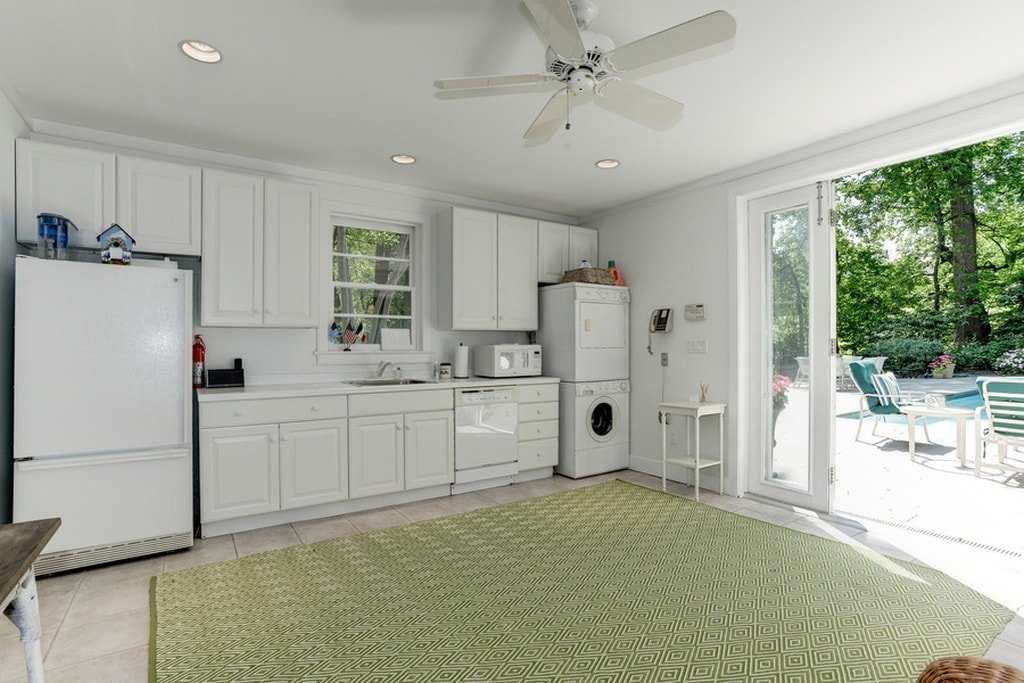 This other kitchen has a consistent white to its cabinetry, walls and ceiling. These are augmented by the large open wall that brings in natural lighting and provides access to the backyard pool. Image courtesy of Toptenrealestatedeals.com.