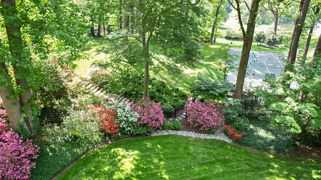 This aerial view of the garden showcases its colorful flowers and shrubs that complement the grass lawn and trees. Image courtesy of Toptenrealestatedeals.com.