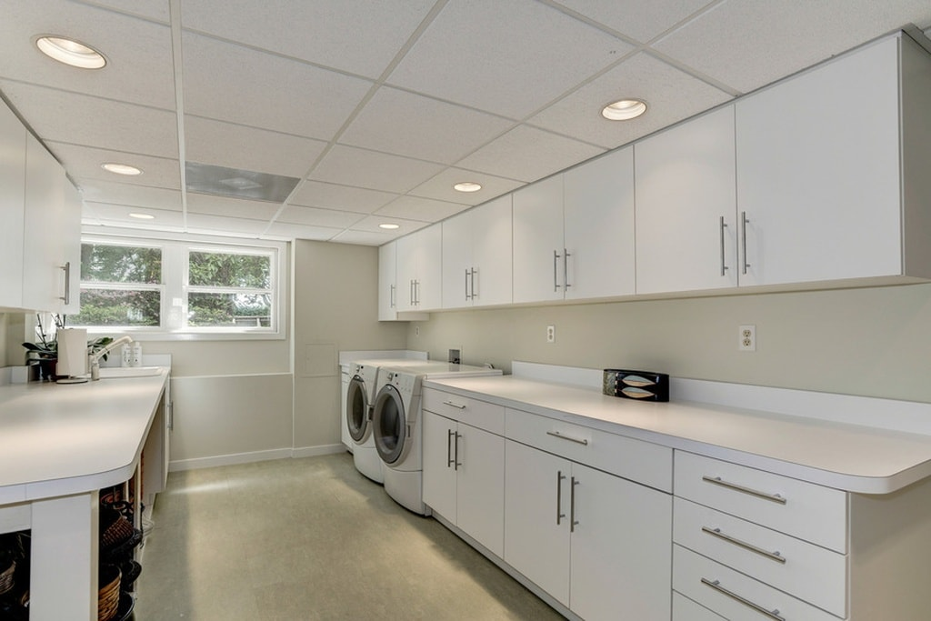 The laundry room has its appliances embedded into the white cabinetry that line the walls. These match well with the white walls, white ceiling and beige floor. Image courtesy of Toptenrealestatedeals.com.
