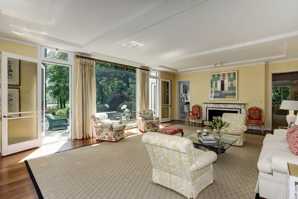 This is the living room that has light tones to its sofas and armchairs to match the bright walls and ceiling. These are augmented by the natural lights coming in from the open walkways that lead to the back. Image courtesy of Toptenrealestatedeals.com.