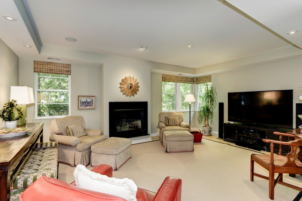 This media room has comfortable cushioned arm chairs with their own foot stools that blend with the beige carpet. These are then contrasted by the fireplace and the large TV. Image courtesy of Toptenrealestatedeals.com.