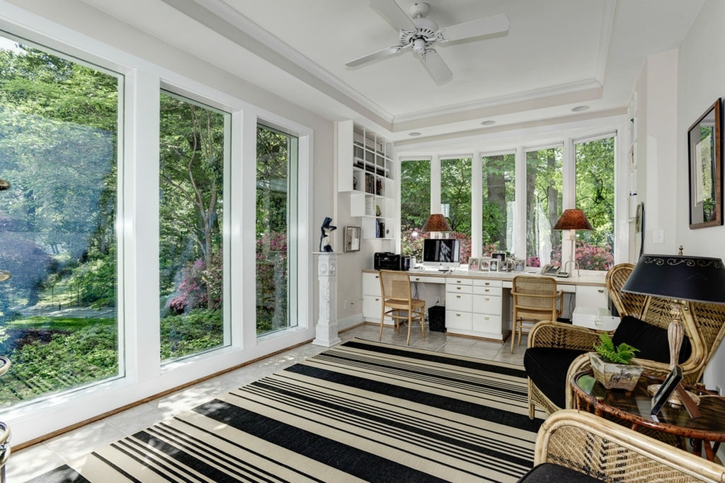 This home office has bright white walls and ceiling that blend with the built-in desk. These are then contrasted by the black and white patterned area rug. Image courtesy of Toptenrealestatedeals.com.