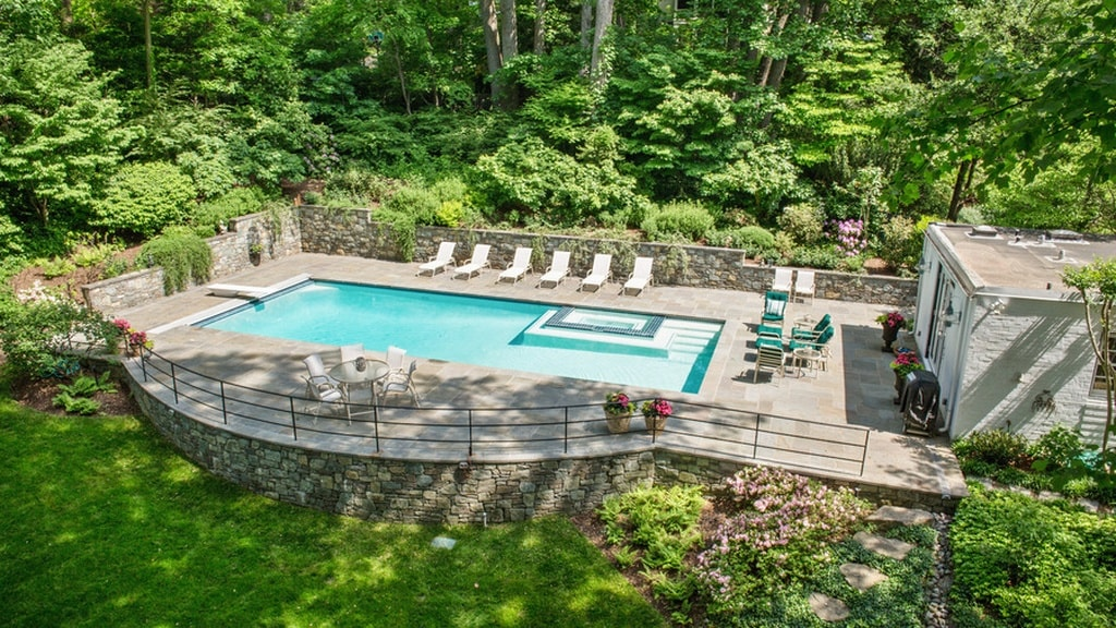 This is an aerial view of the backyard pool. Here you can see that the poolside area is surrounded by low stone walls that separate the area from the surrounding lush landscaping of trees and shrubs. Image courtesy of Toptenrealestatedeals.com.