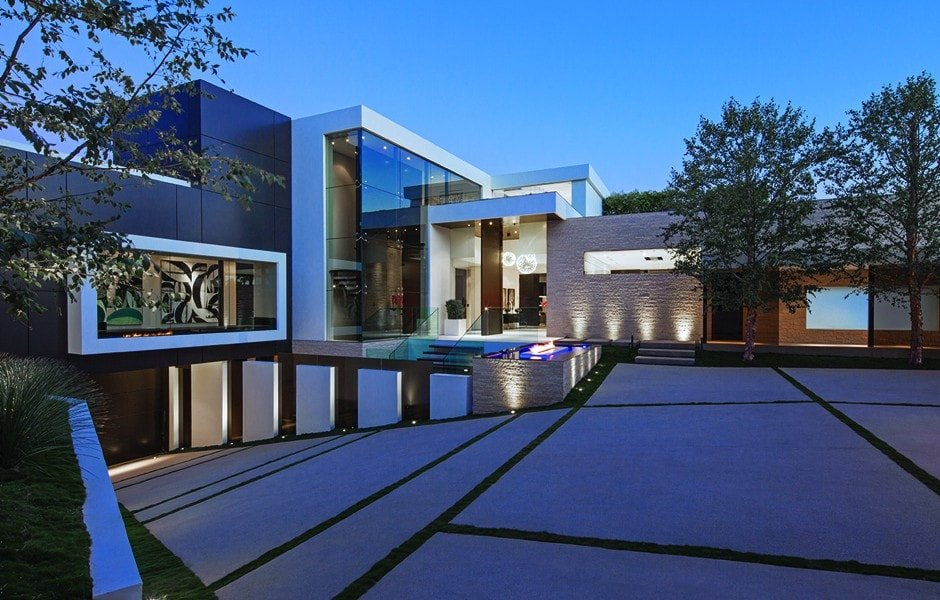 This is a front view of the house showcasing its large glass walls. These give a view of the interiors that are lit with warm lighting to match the outdoor lamps. Image courtesy of Toptenrealestatedeals.com.