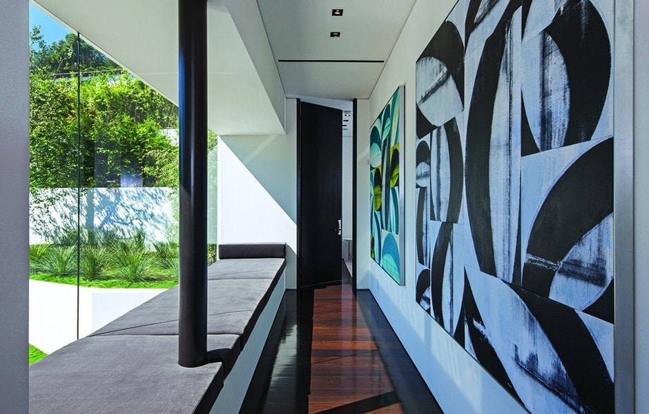 This is the hallway leading to one of the rooms. One one side, you have a glass wall with built-in cushioned benches on the side while the other side is adorned with large colorful paintings. Image courtesy of Toptenrealestatedeals.com.