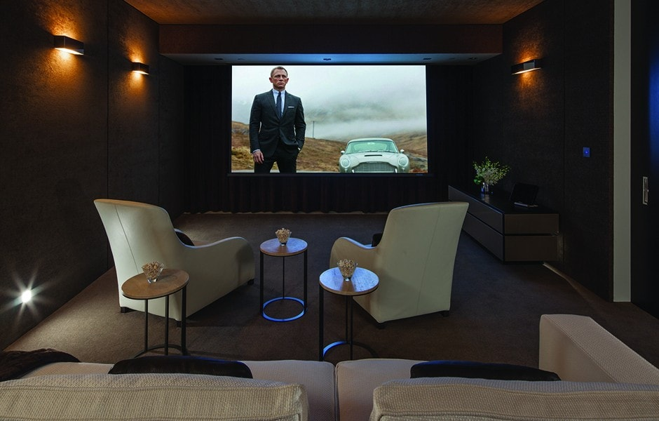 The media room has a couple of comfortable cushioned armchairs facing a large screen. These are paired with personal side tables for refreshments. Image courtesy of Toptenrealestatedeals.com.