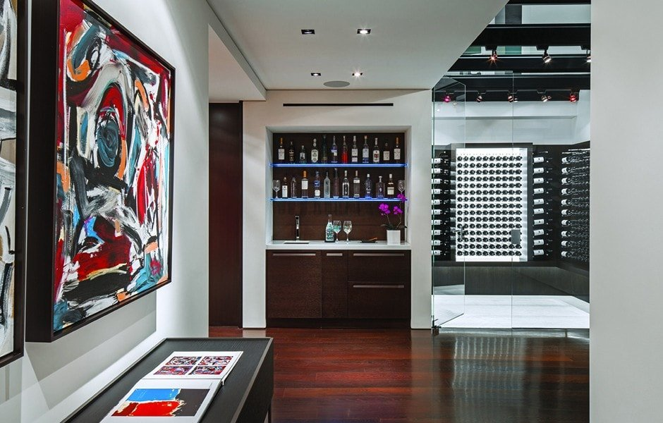 Here you can see the wine cellar of the house with a modern look to its storage for wine bottles. Next to it is a small bar with dark brown cabinetry that matches the dark hardwood flooring. Image courtesy of Toptenrealestatedeals.com.