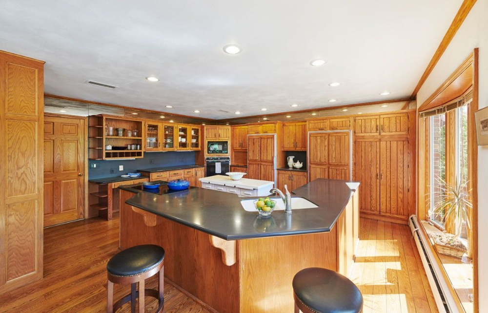 Kitchen with built-in shelving, a white center island and a breakfast bar island. Image courtesy of Toptenrealestatedeals.com.