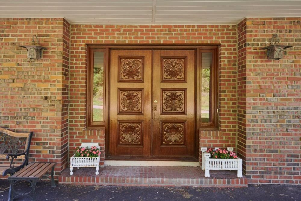 The home features a stunning main door surrounded by the red brick walls. Image courtesy of Toptenrealestatedeals.com.