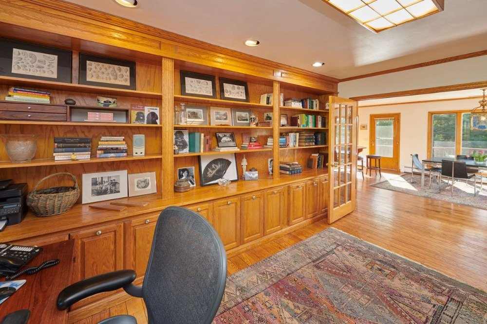 Home office with brown built-in cabinetry and shelving. Image courtesy of Toptenrealestatedeals.com.