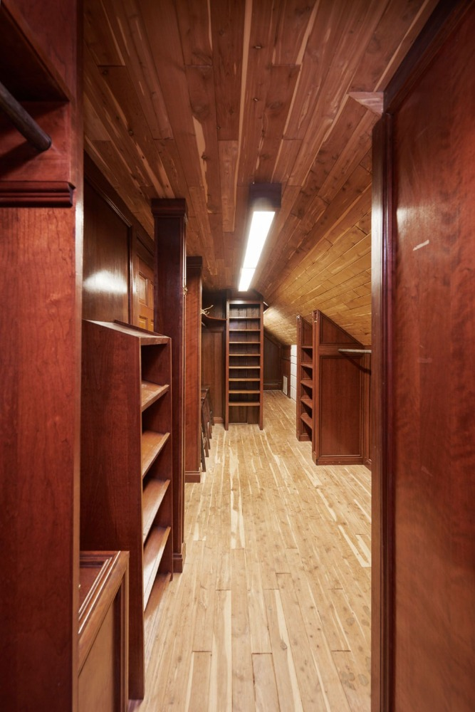 A look at the walk-in closet with brown cabinetry and shelves. Image courtesy of Toptenrealestatedeals.com.