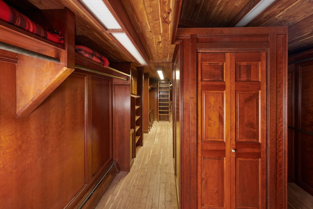 Walk-in closet featuring brown walls and a rustic ceiling. Image courtesy of Toptenrealestatedeals.com.