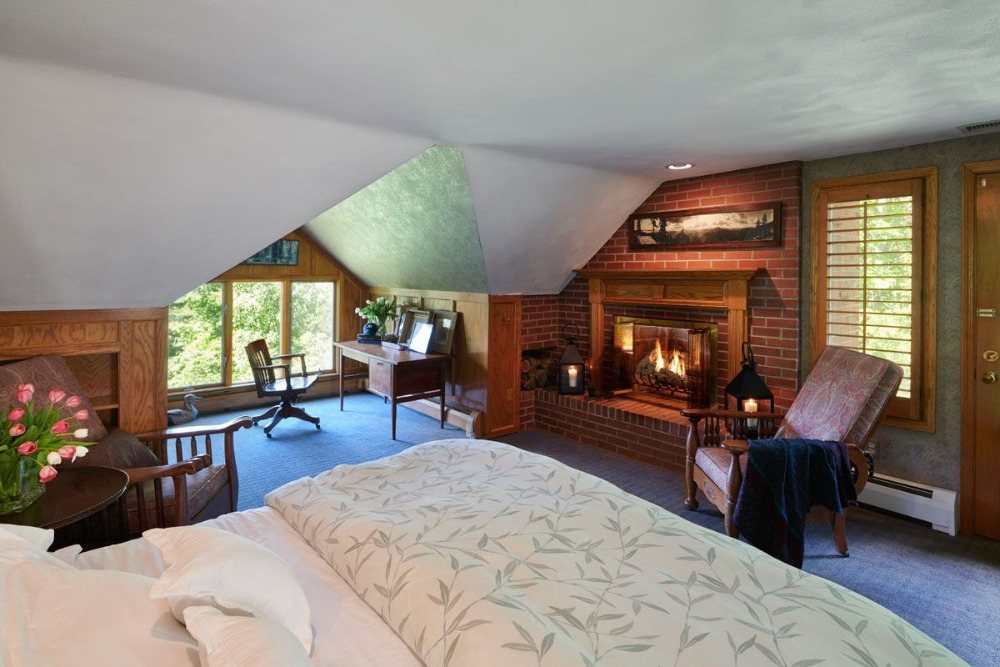 A bedroom suite offering a nice comfy bed, a desk and a chair by the windows and a fireplace. Image courtesy of Toptenrealestatedeals.com.