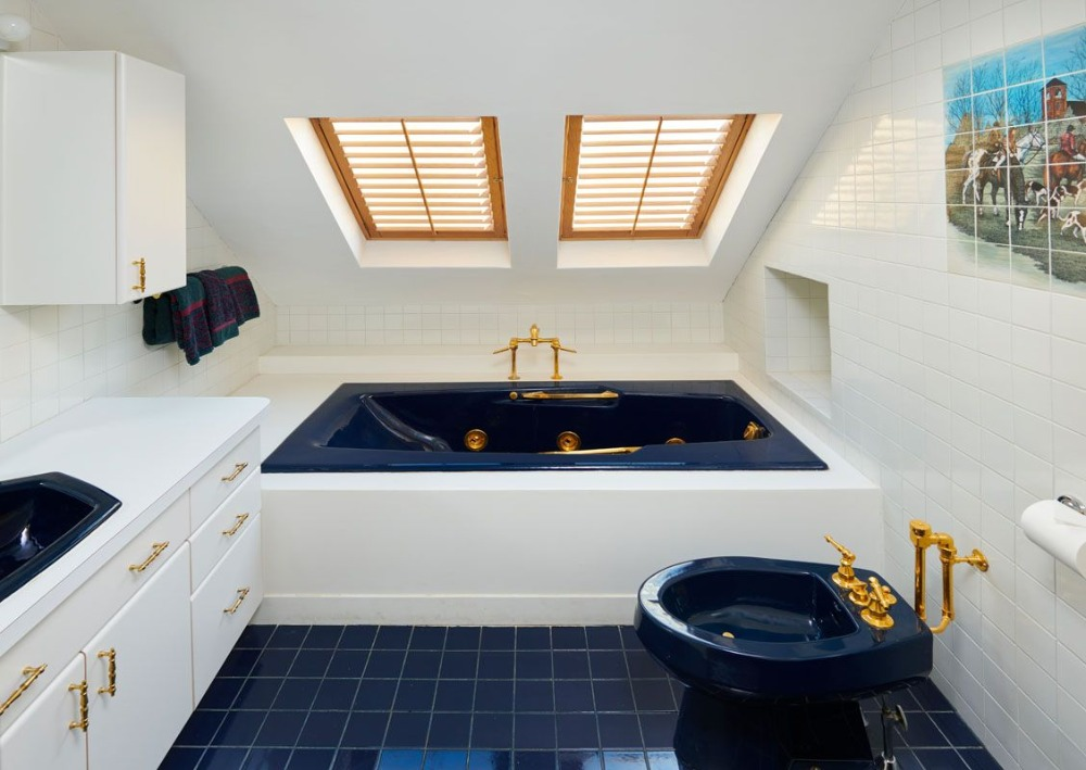 One of the bedroom's bathroom featuring a white sink counter matching the drop-in soaking tub. Image courtesy of Toptenrealestatedeals.com.
