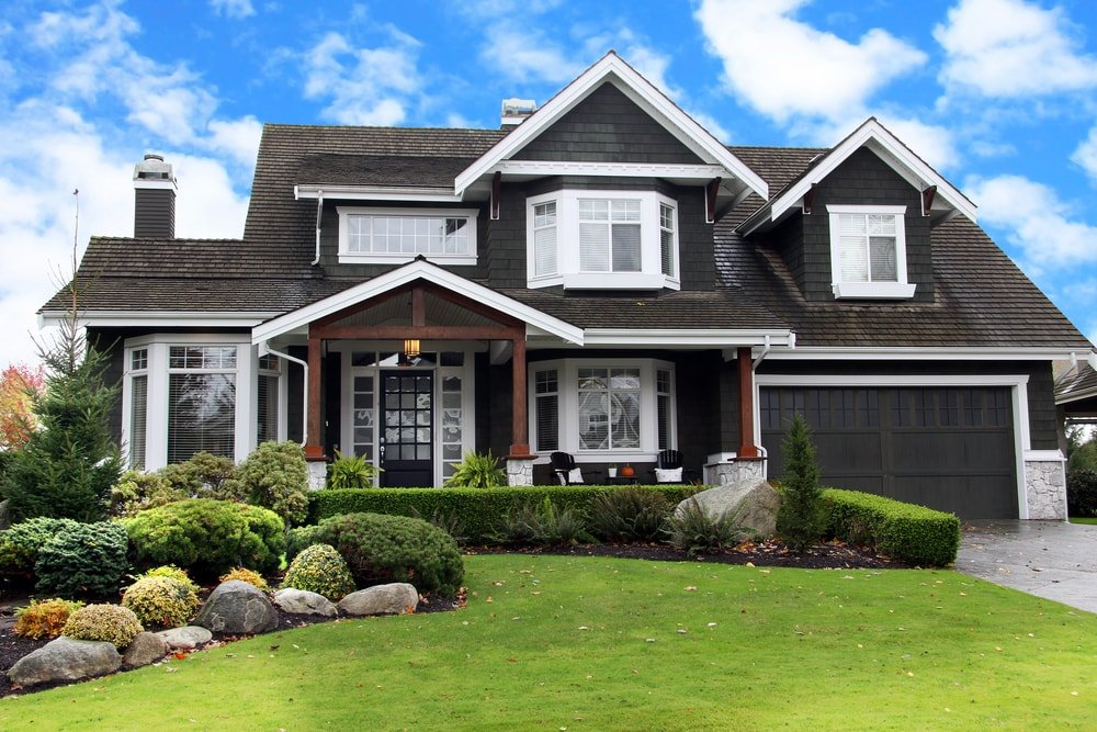 Suburban upscale house with a largely black exterior and a landscaped front lawn in a Canadian neighborhood.