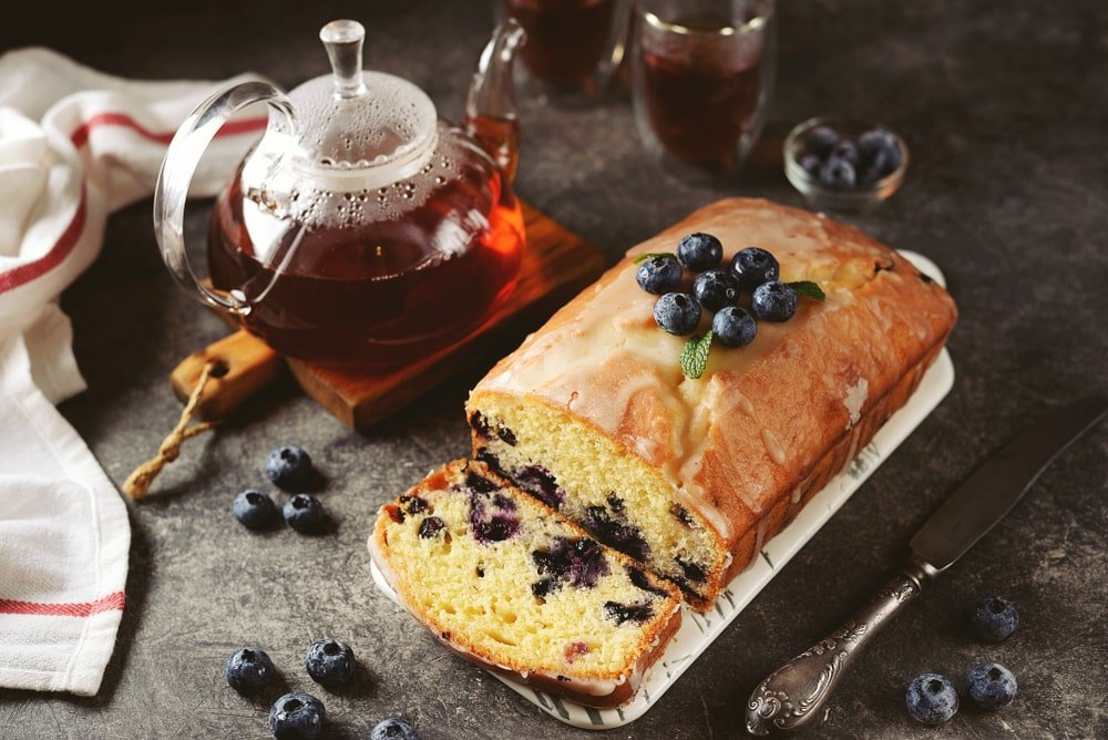 Blueberry cake beside a sprinkle of blueberries and a pitcher and glasses of honey.