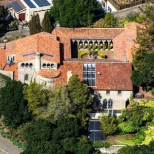 This is an aerial view of the house with a French Medieval Cloister design and terracotta-toned roof.