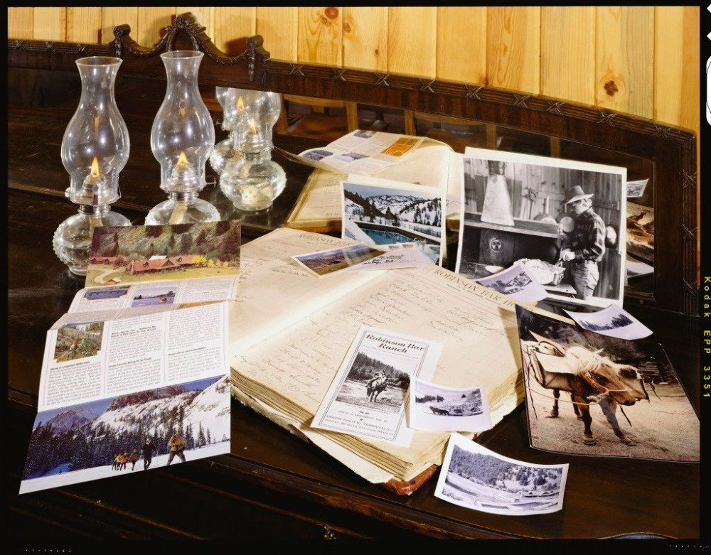 Closer look at some photographs, a notepad and candle lights in glasses on top of a rustic table. Image courtesy of Toptenrealestatedeals.com.