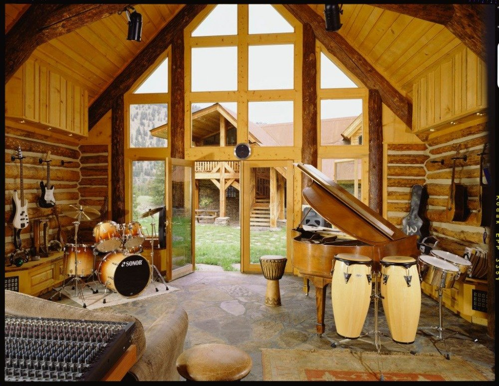A music studio with a drum set, a wooden piano and multiple guitars hanging on the wall. Image courtesy of Toptenrealestatedeals.com.