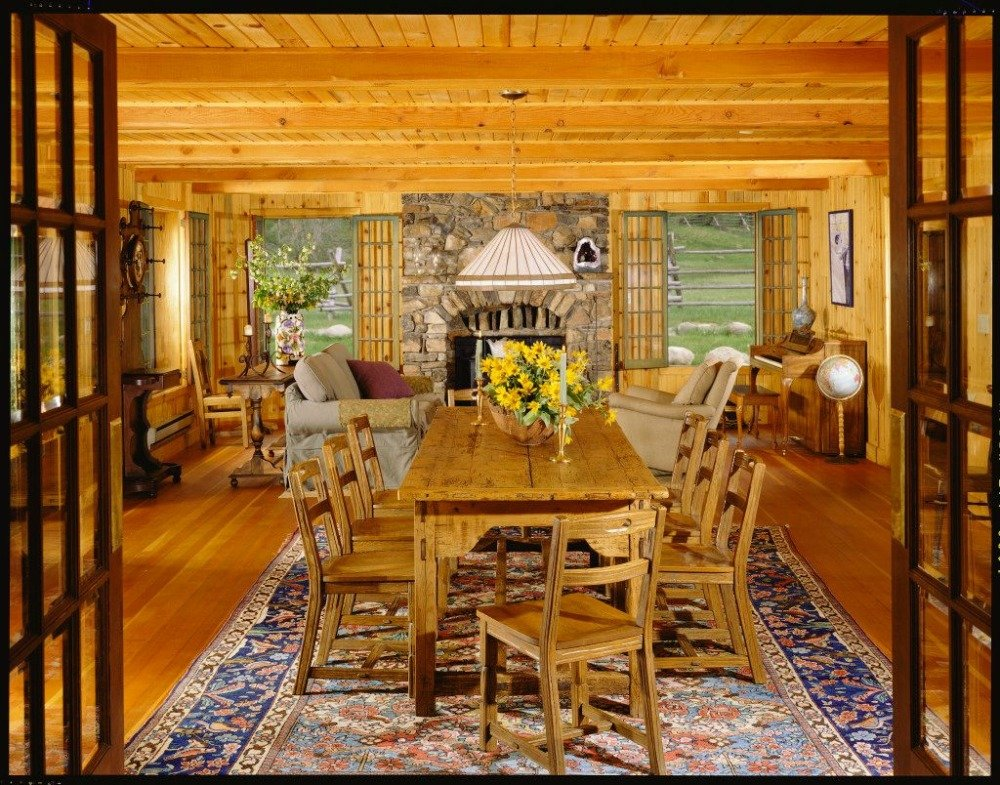 A great room featuring a cozy living space with a fireplace and a wooden dining table and chairs set on top of the area rug. Image courtesy of Toptenrealestatedeals.com.