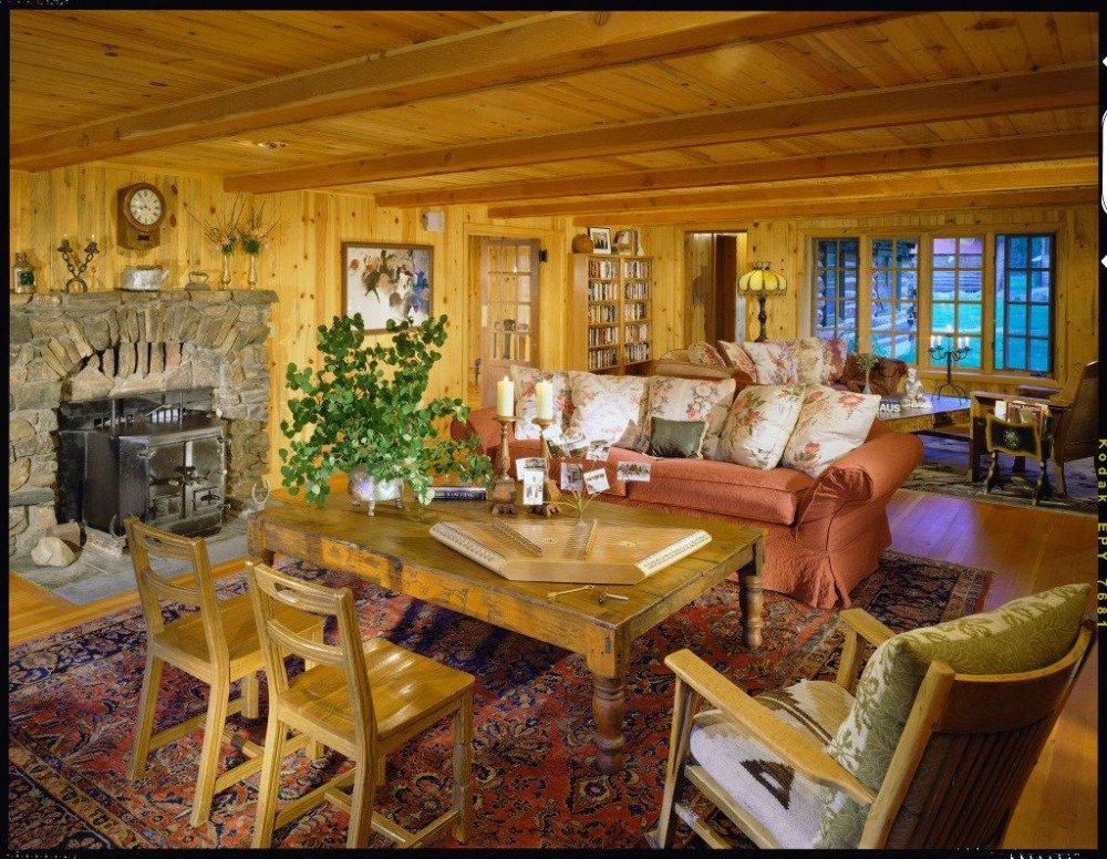 Living space with a nice comfy couch, a rustic center table along with three armchairs and a stone fireplace. Image courtesy of Toptenrealestatedeals.com.