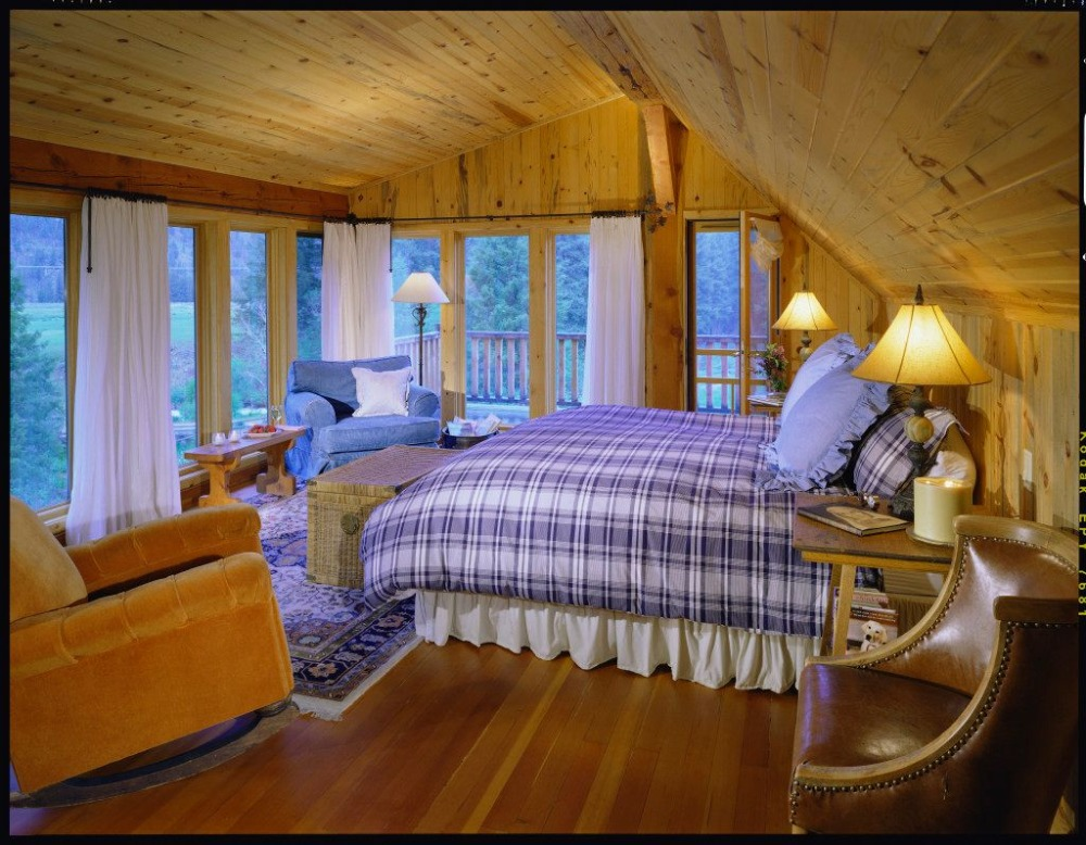 Bedroom with a cozy bed set facing the stunning outdoor surroundings through the glass windows. Image courtesy of Toptenrealestatedeals.com.