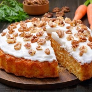 A freshly-baked carrot cake topped with icing and walnuts.