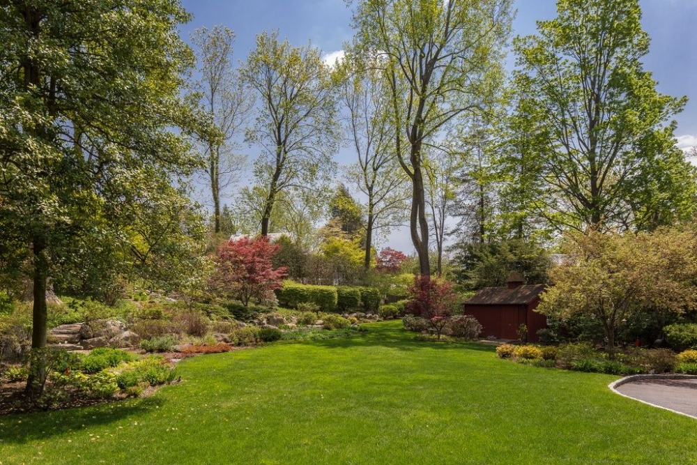 A look at the home's backyard garden with lush lawns, plants and trees. Images courtesy of Toptenrealestatedeals.com.