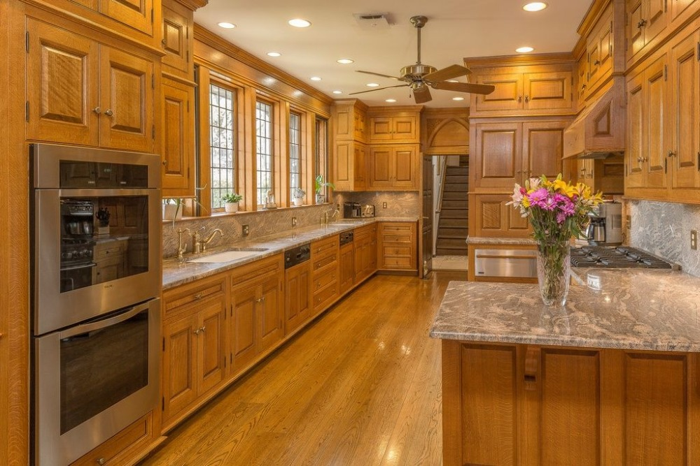 Spacious kitchen with brown cabinetry and a stunning kitchen countertop. Images courtesy of Toptenrealestatedeals.com.