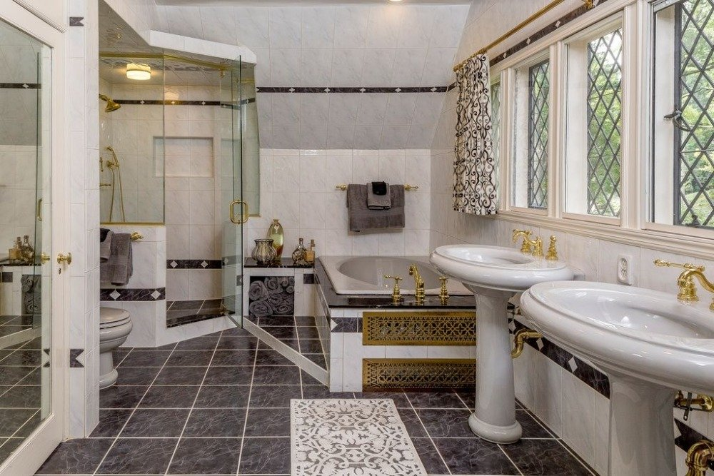 Primary bathroom featuring a walk-in shower room and an elegant drop-in soaking tub. There's a couple of pedestal sink as well. Images courtesy of Toptenrealestatedeals.com.