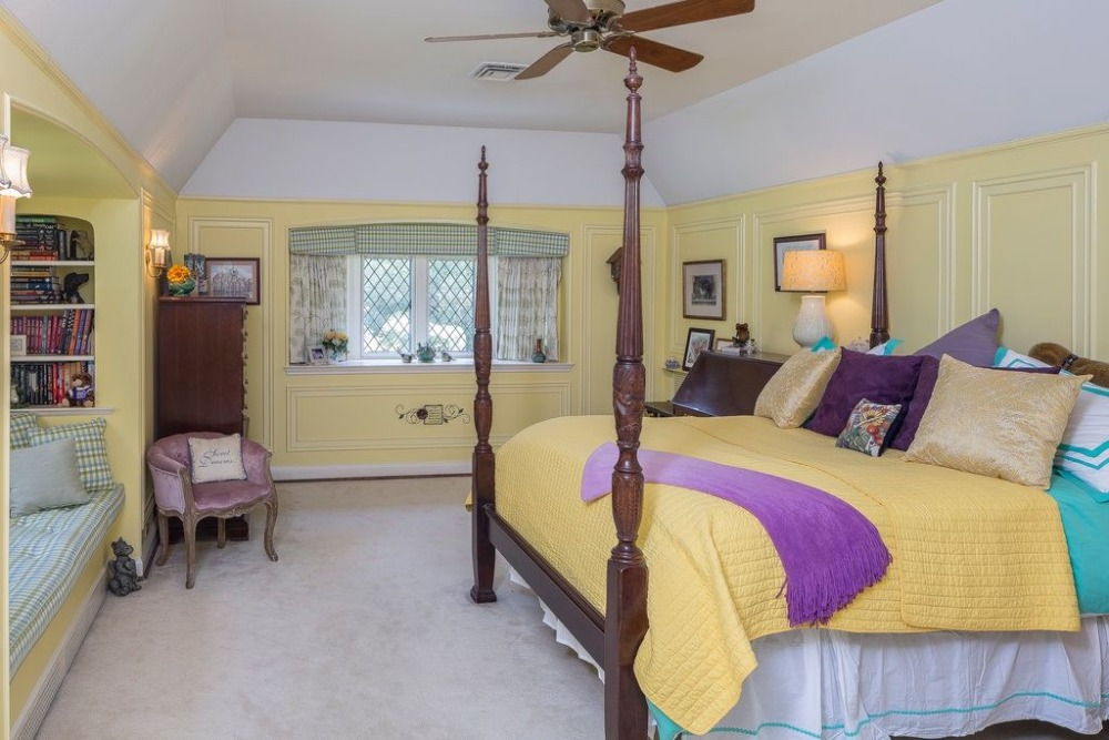 Bedroom with yellow walls and carpeted flooring. There's a reading nook by the window with built-in shelving. Images courtesy of Toptenrealestatedeals.com.