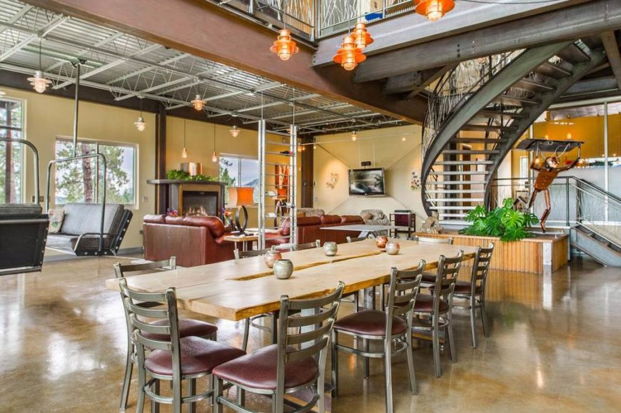 This is the view of the great room from the vantage of the dining area. Here you can see the living room that has a fireplace on the far corner. This angle also shows the metal curved staircase adorned with a metal sculpture on the side. Image courtesy of Toptenrealestatedeals.com.