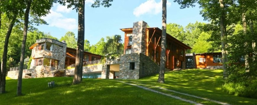This is a view of the house from the back. Here you can see that the house is a combination of stone and wooden structures that are complemented by the lush landscaping of tall trees and well-maintained grass lawns. Image courtesy of Toptenrealestatedeals.com.