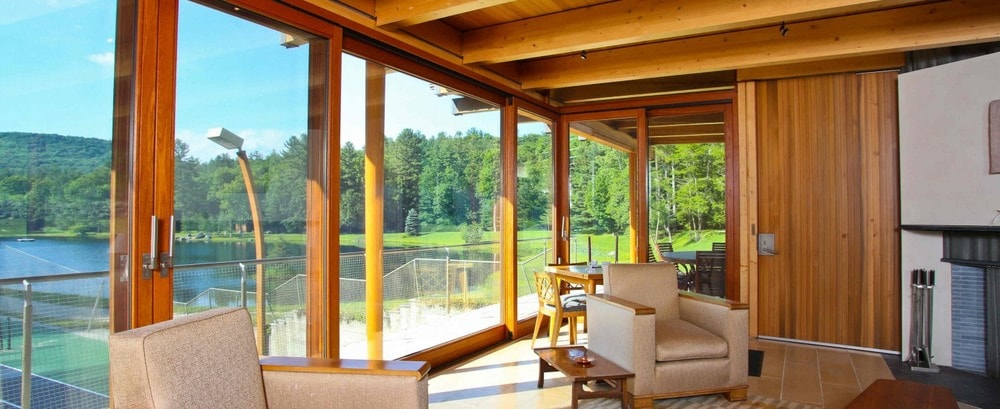This is the second floor of the wooden house beside the tennis court. This is fitted with armchairs illuminated by the glass walls adorned by wooden pillars and wooden beams of the ceiling. Image courtesy of Toptenrealestatedeals.com.