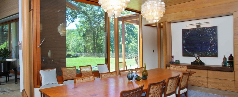 This is the dining area with a long wooden dining table topped with chandeliers. These are then complemented by the natural lights and green scenery afforded by the glass wall. Image courtesy of Toptenrealestatedeals.com.