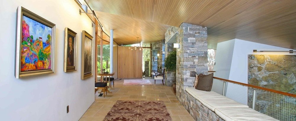 This is the foyer of the house with an arched wooden ceiling to complement the mosaic stone walls and pillars with a built-in bench on the side. . Image courtesy of Toptenrealestatedeals.com.