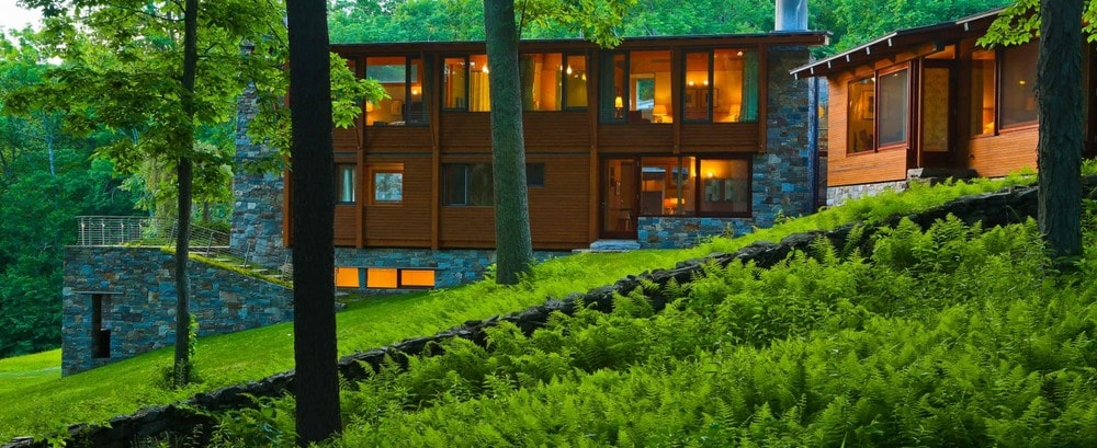 This is a view of the house from the vantage of the surrounding lush landscape of tall trees and grass. These make the wooden exterior walls of the house stand out complemented by the warm glow of the glass walls and windows. Image courtesy of Toptenrealestatedeals.com.