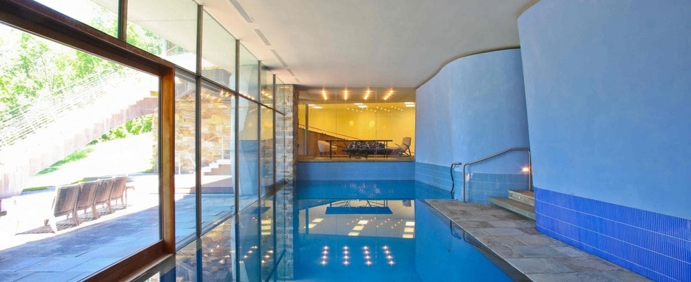 This is the indoor pool of the house with a large glass wall on one side to bring in an abundance of natural lighting. Image courtesy of Toptenrealestatedeals.com.
