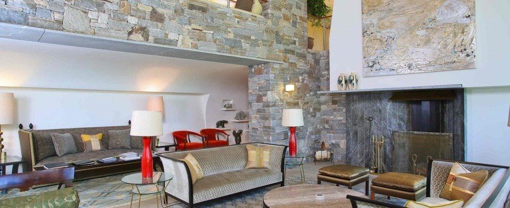 This is the formal living room with cushioned couches adorned by the mosaic stone walls and the large fireplace topped with a large wall-mounted artwork. Image courtesy of Toptenrealestatedeals.com.