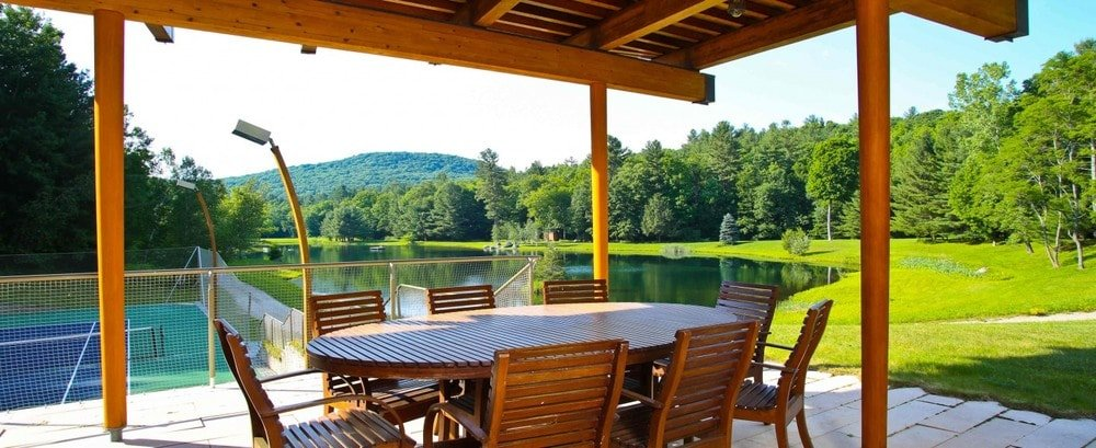 This is the covered patio fitted with an outdoor dining set that matches the wooden ceiling. This has a sweeping view of the lake along with the tall trees surrounding it. Image courtesy of Toptenrealestatedeals.com.