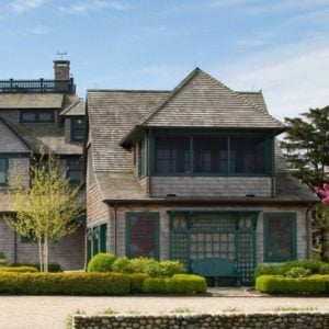 This is the front view of the main house. You can see here the Victorian-style exteriors that are complemented by the landscaping of shrubs and a colorful tree on the side. Image courtesy of Toptenrealestatedeals.com.