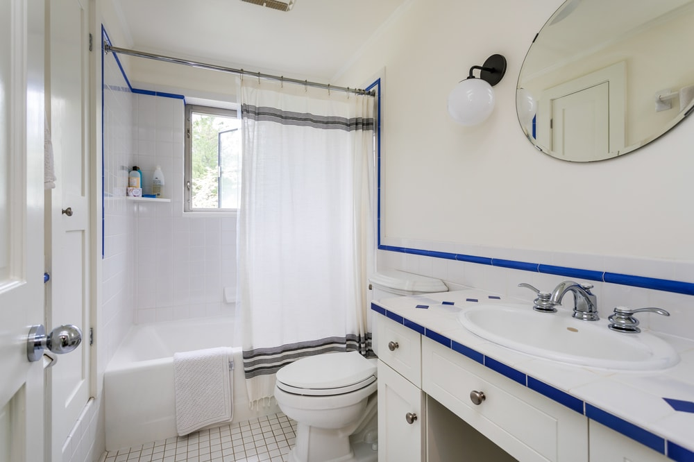 This simple bathroom has blue lining accent that stands out against the light beige tone of the walls, tiles and ceiling. Image courtesy of Toptenrealestatedeals.com.
