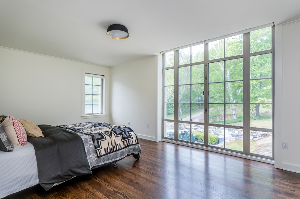 This bedroom has a large set of glass doors across from the gray bed that stand out against the white walls and dark hardwood flooring. Image courtesy of Toptenrealestatedeals.com.